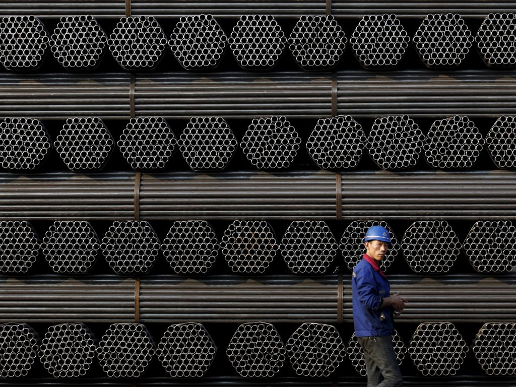 A Chinese worker walks by piles of steel.