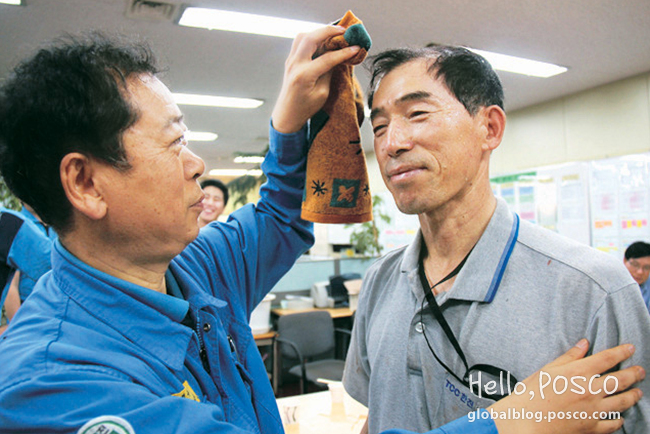 A Pohang Steelworks employee is wiping the face of his fellow employee from TCC Hanjin