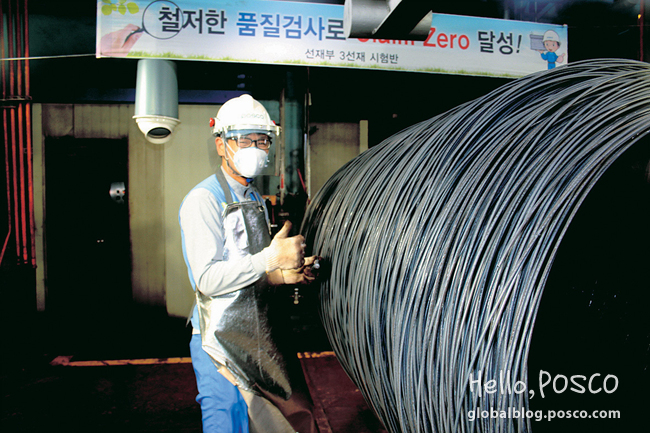 An employee at Pohang 3rd Wire Rod Factory gives a thumb-up while checking flaws on 200℃ hot coils