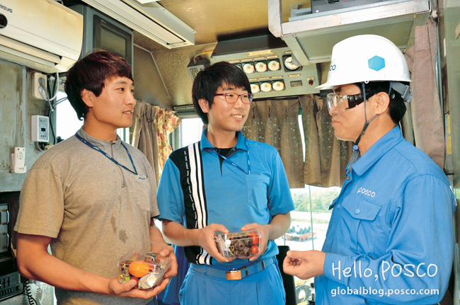 Employees at a shipping crane are given encouraging refreshments from a colleague at Gwangyang Steelworks' Manufacturing Technology Department