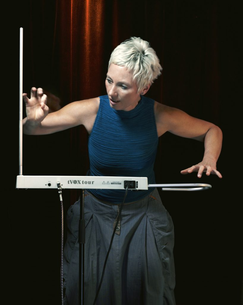 Barbara Buchholz plays the theremin with her hands gliding over the metal antennae