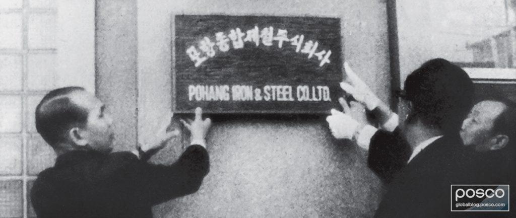 POSCO executives hang a sign on their headquarters