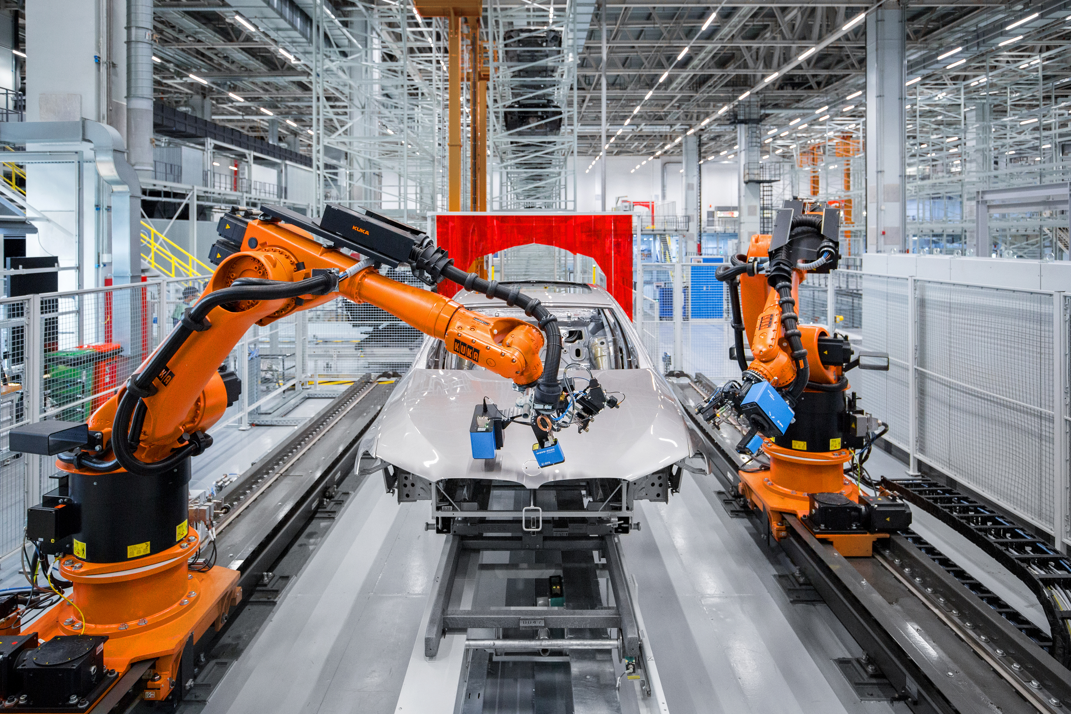 Two automated robots paint the BMW on the factory line.