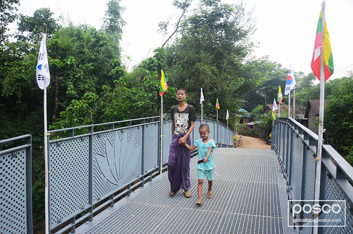 A man and young girl crossing the Yoewa steel bridge built by POSCO 1% Sharing Foundation