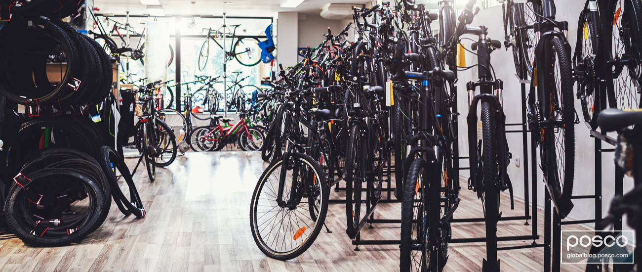 Numerous bikes sit on racks in an empty retail store