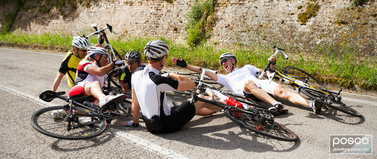 Five cyclists sit and lie on a paved road to take a break from cycling