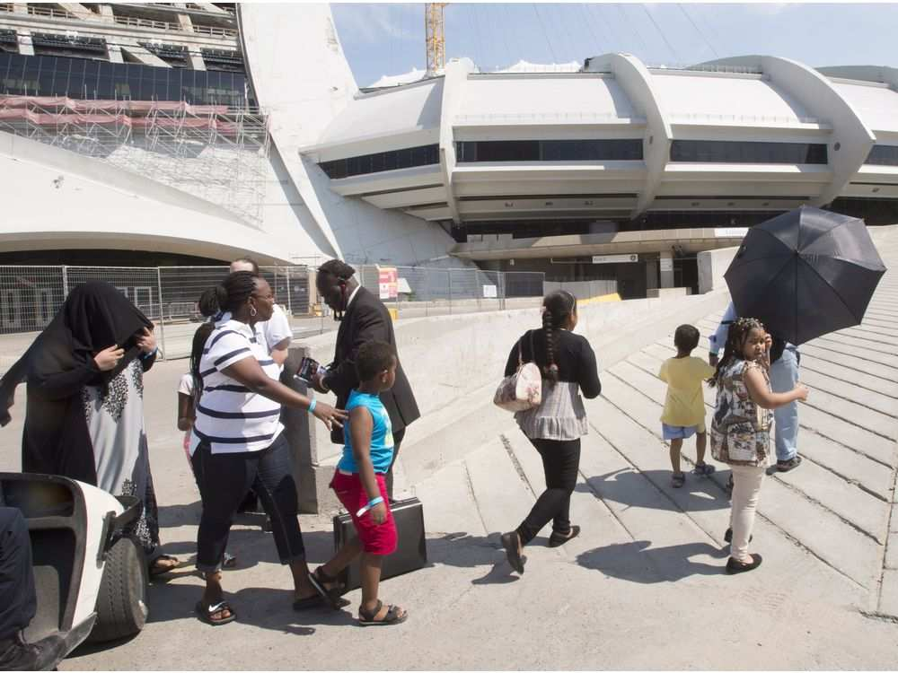 A group of asylum seekers leave the Olympic Stadium in Montreal, Canada, to go for a walk