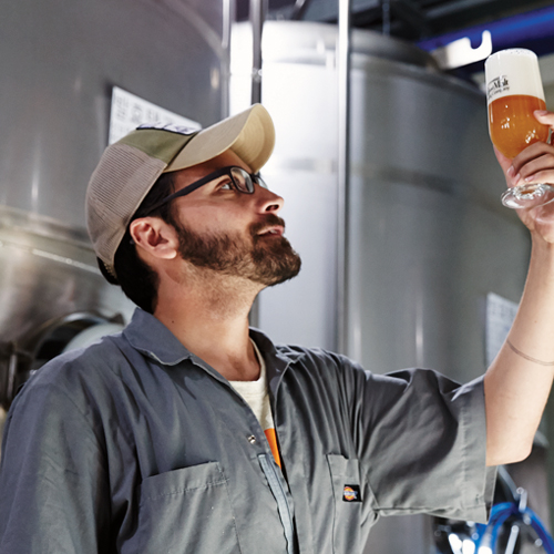 Brandon Fenner, Head Brewer at the Hand and Malt Brewing Company, holds up a glass of beer