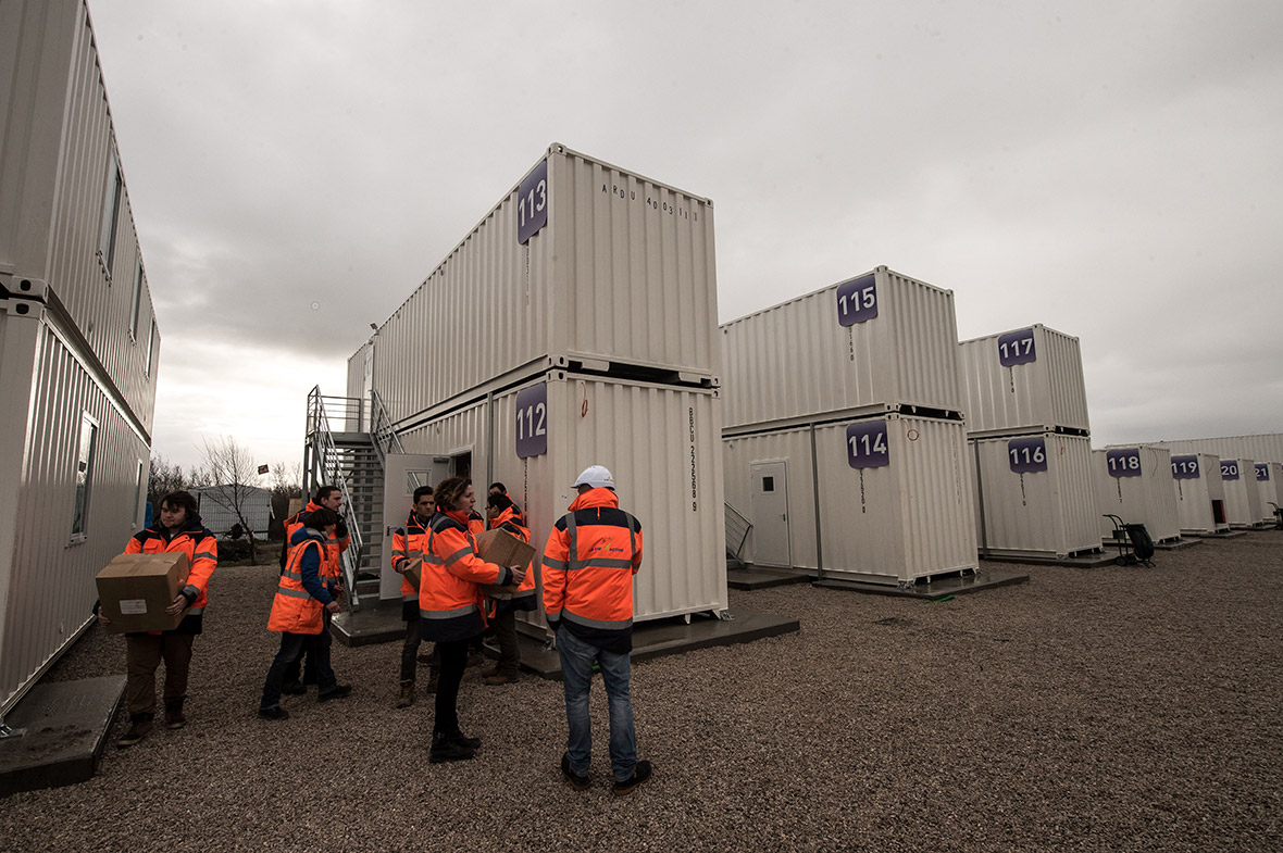 Aid workers move materials in and out of the shipping container shelters