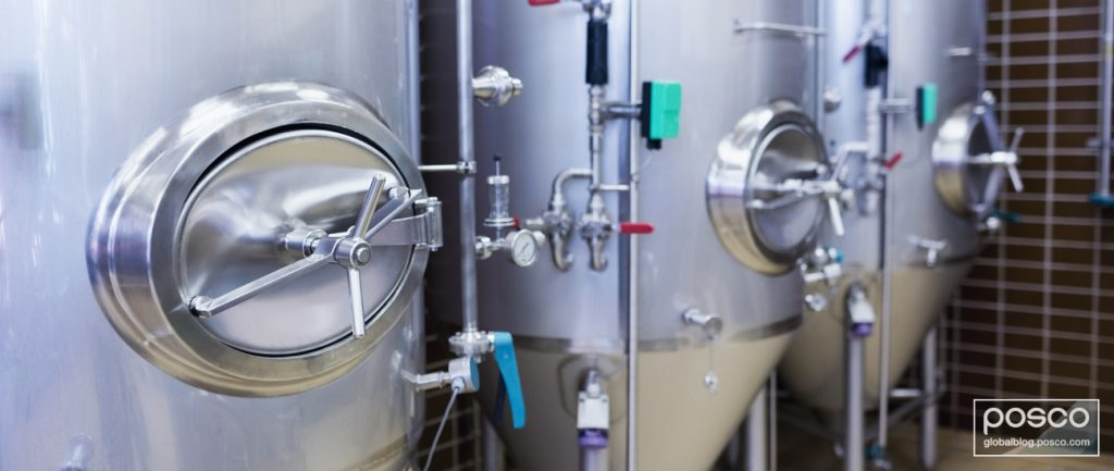 Three large stainless steel vessels for beer in a brewery