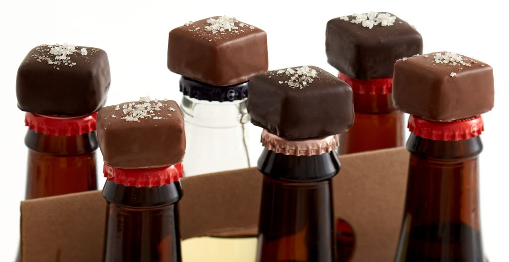 Chocolates placed on top of six bottles of beer