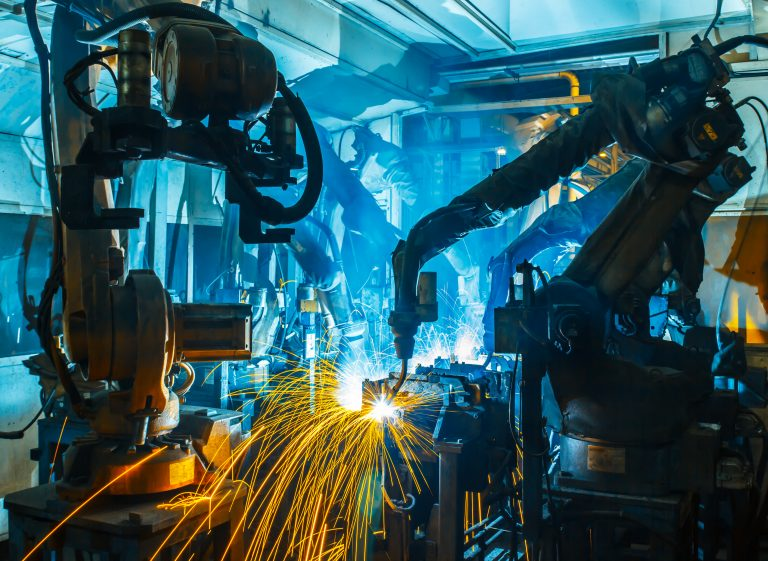 Robotic arms work on a steel assembly line.