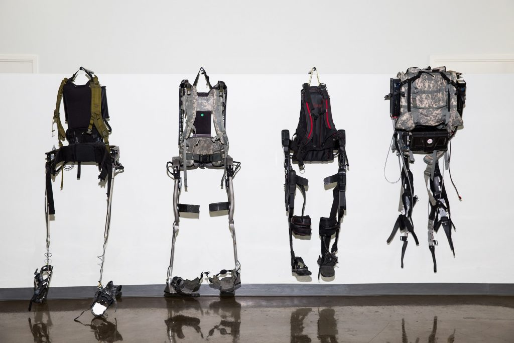 Four different types of exoskeletons for workers and military personnel hang on display.