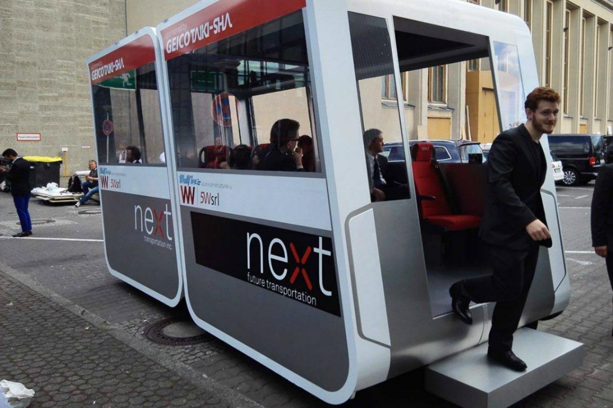 A man steps out of a Next Future Transportation autonomous pod