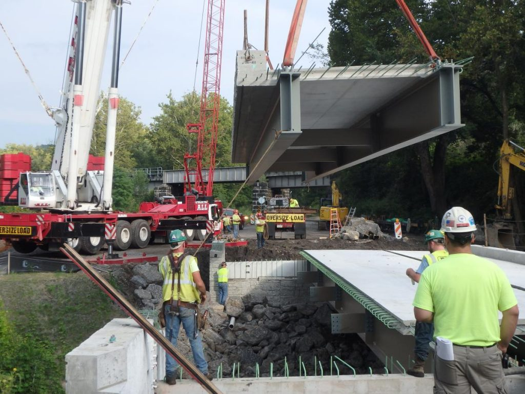 Workers assemble a prefabricated bridge in Pennsylvania, U.S. to replace a structurally deficient bridge