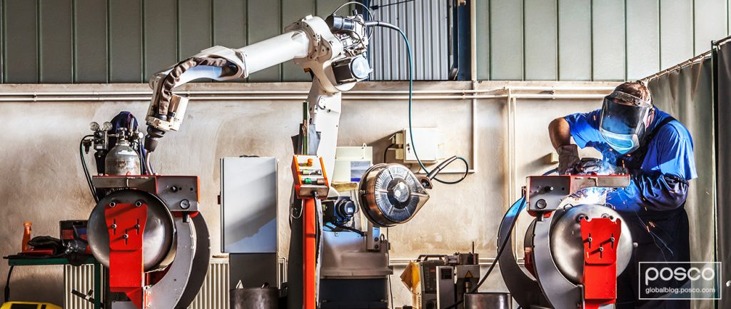 A welder gets help from a cobot as he pieces together metal
