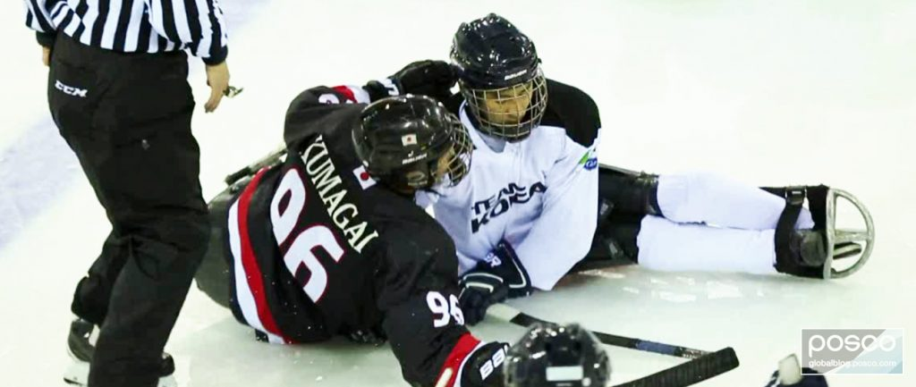 A Korean National Para Ice Hockey Team player fights for the puck during a game against Japan.