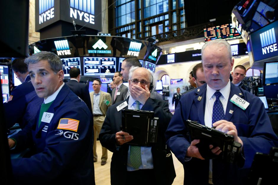 Three men on Wall Street stare at stock prices on screens in disbelief