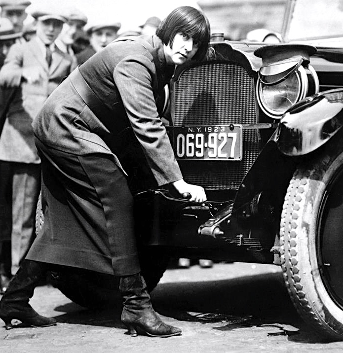 A woman cab driver cranks her car on the streets of New York in 1923