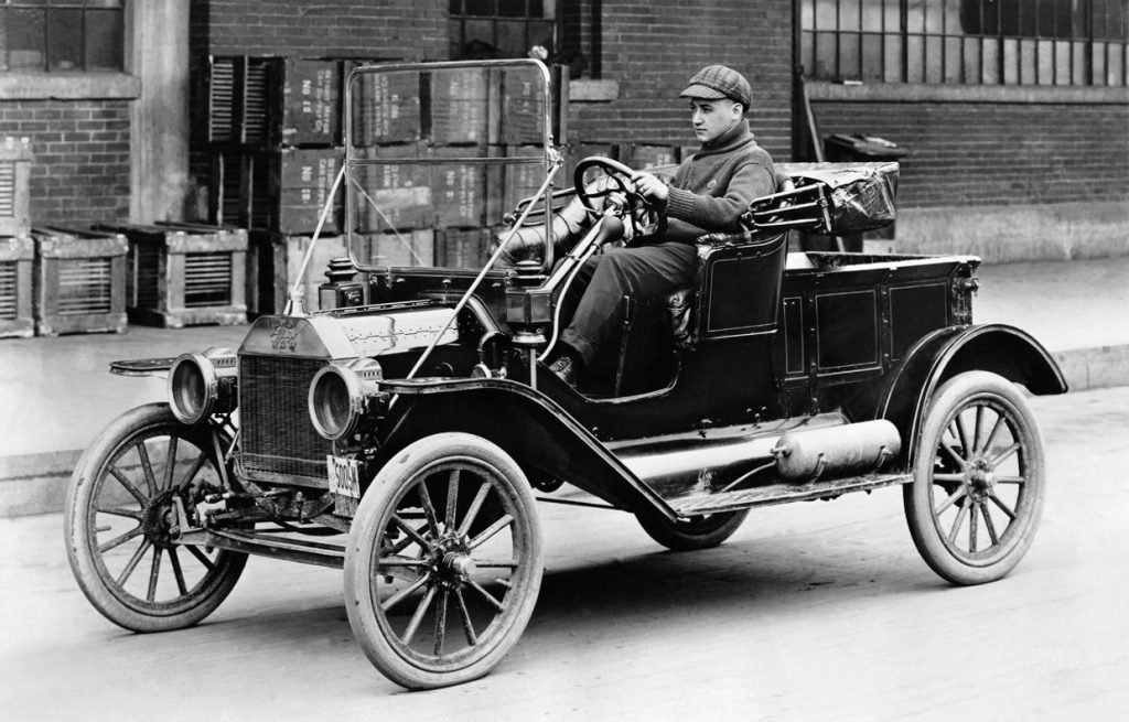 A man drives a Ford Model T in the 1920s.