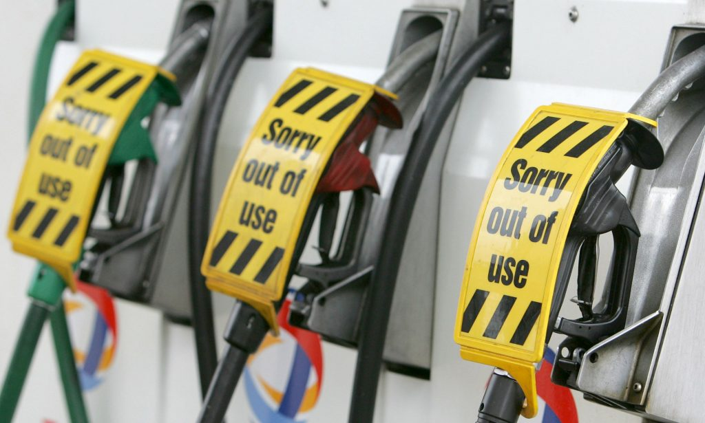 """Three gasoline pumps with the signs """"Sorry out of use"""" on them."""