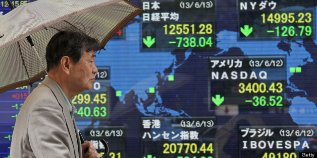 A Japanese man with an umbrella walks in front of a display showing falling stock prices.