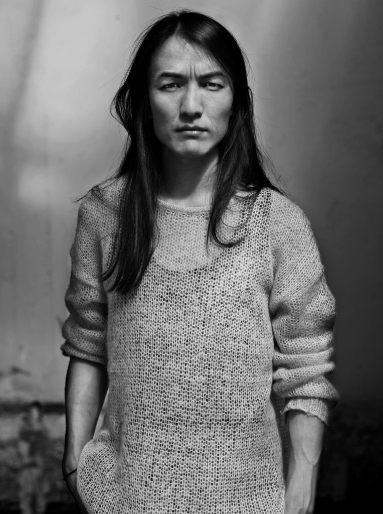 A black and white portrait of fashion designer Naim Josefi.