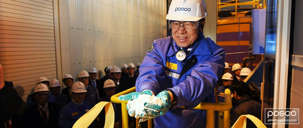 POSCO CEO Kwon Ohjoon holds lithium in both his hands while employees watch on at the PosLX, POSCO's battery production factory for mining lithium.