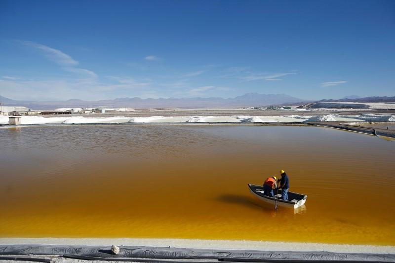 Two workers in a boat take samples of brine at the Rockwood Plant for mining lithium.