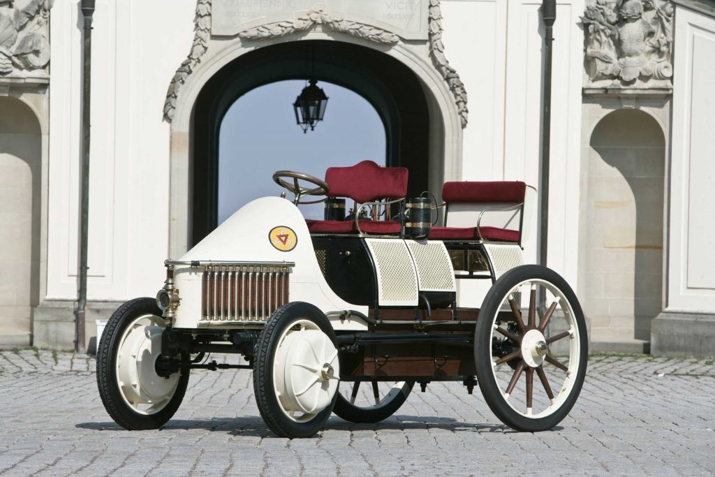 A recreation of the Semper Vivus, the first hybrid EV made by Ferdinand Porsche in white and burgundy.