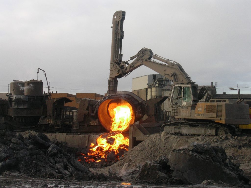 A large vat pours red-hot steel slag into a pile to cool.