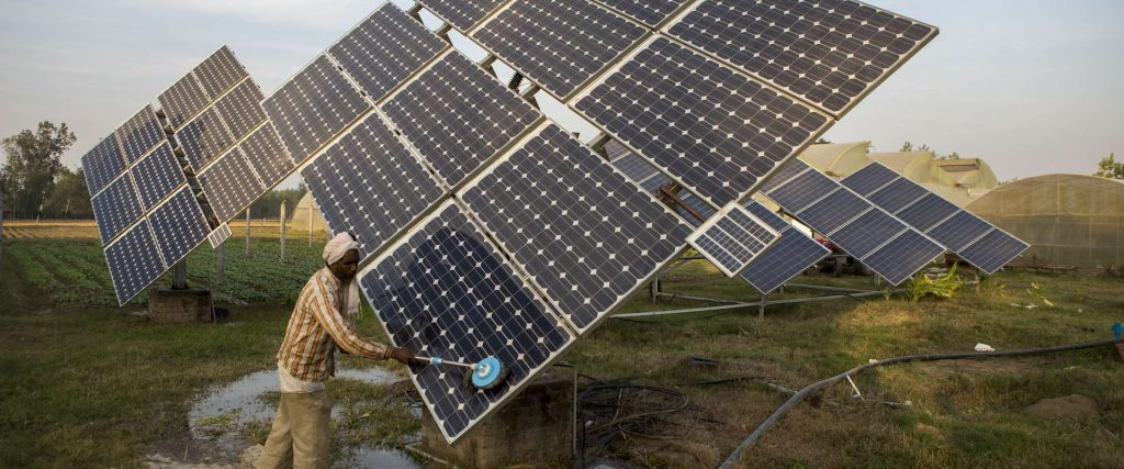 An Indian man cleans a solar panel.