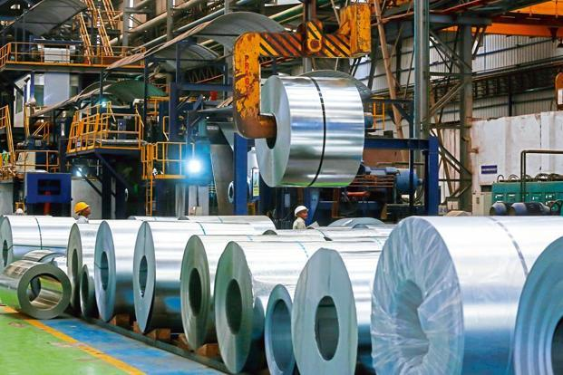 Rolls of steel are in a steel mill.