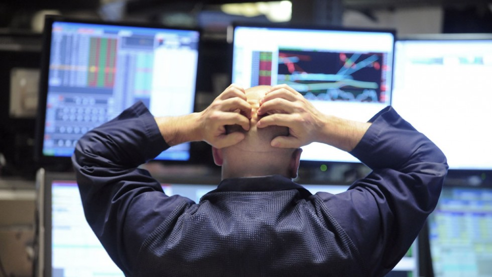 A man on Wall Street sits at his desk with his hands on the back of his head staring at his computer screens that show financial stocks.