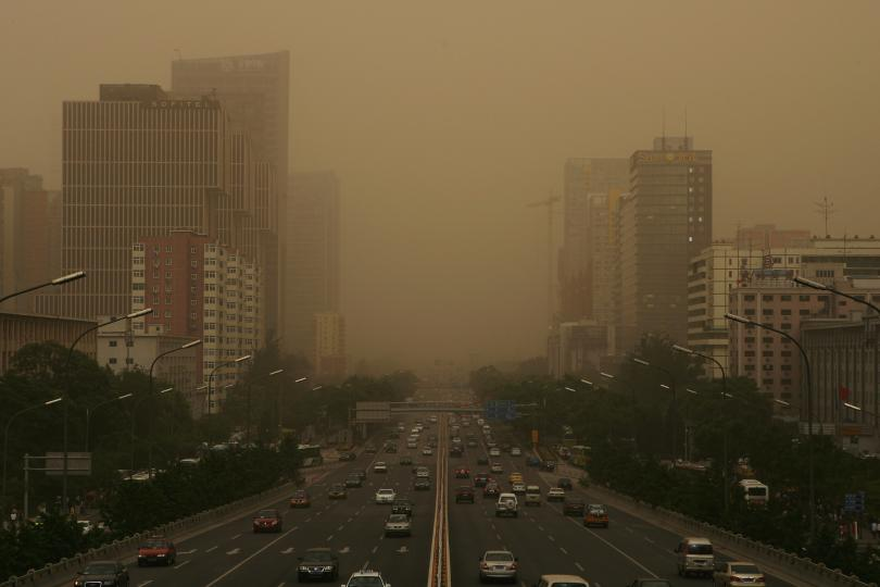 A city with roads and buildings is filled with brownish smog.