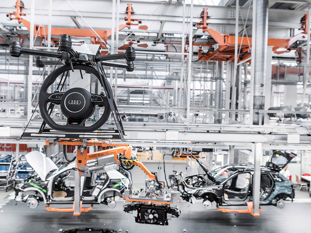 Drones transport car parts in Audi's factory.