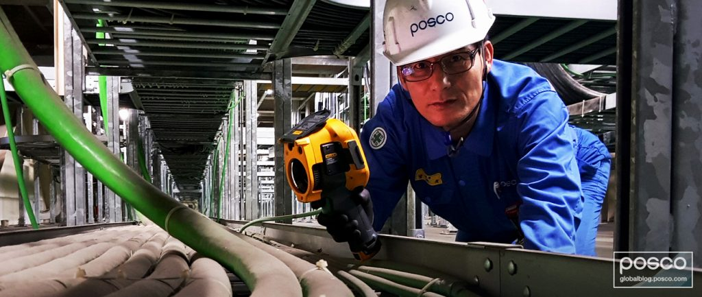Nam Tae-Gyu examines machinery at a POSCO steel mill.