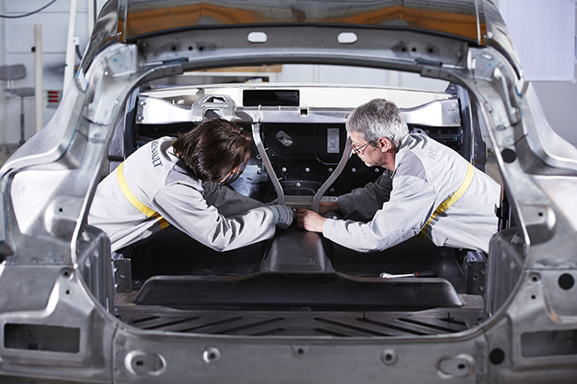 Two technicians work on a car.