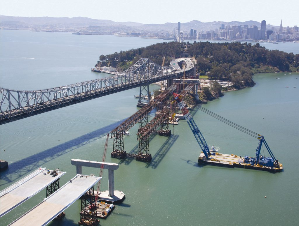 A floating crane lifts prefabricated deck sections onto the San Francisco-Oakland Bay Bridge.
