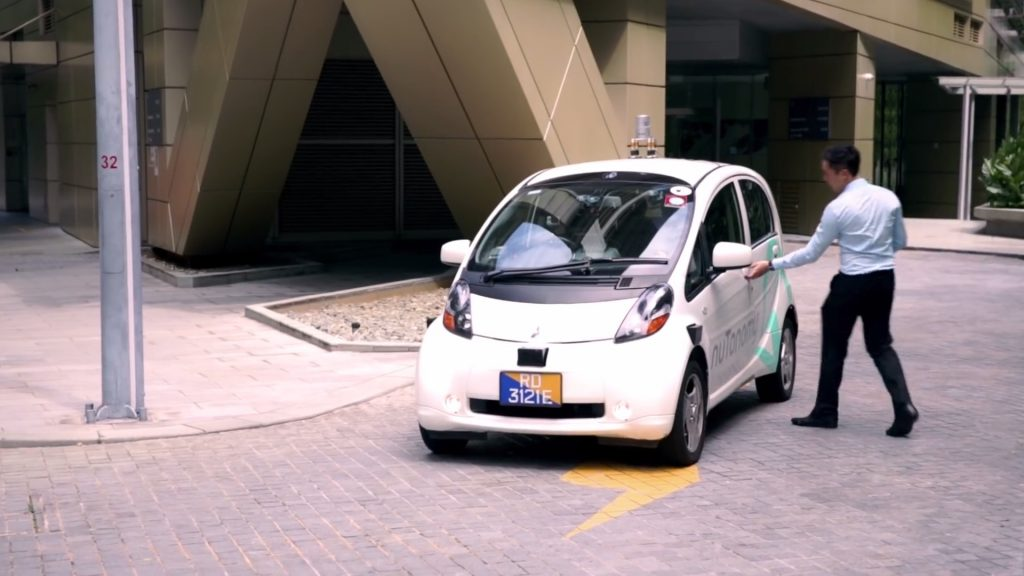 A man is opening the door to one of nuTonomy's autonomous taxis in Singapore.