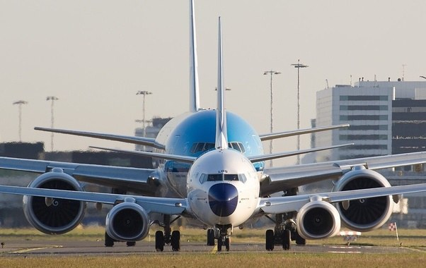 Aviation frontal view of a large plane behind a smaller plane.