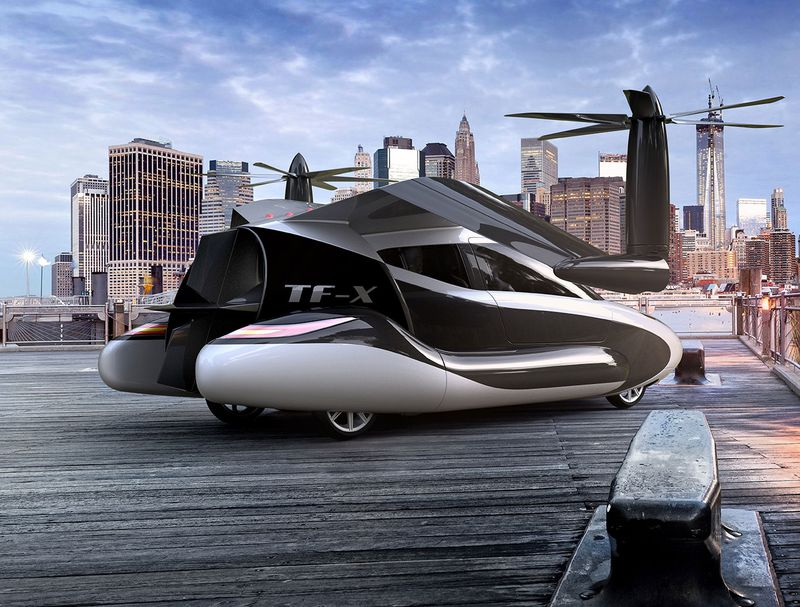 A TF-X flying car is parked outside in a city.