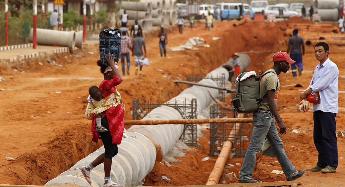 People cross an underground pipeline construction site in Angola.