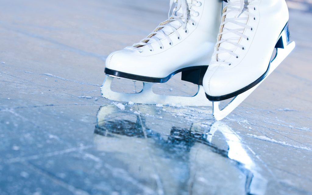 A pair of white figure skates on ice.