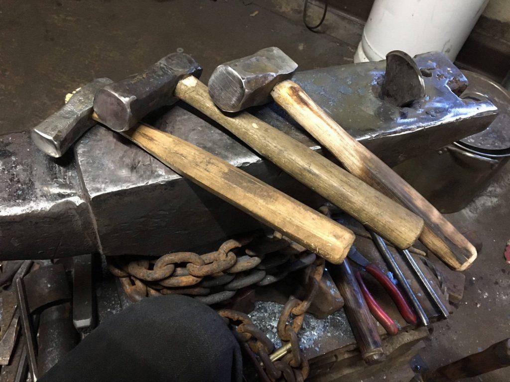 Three hammers resting on a blacksmith's anvil.