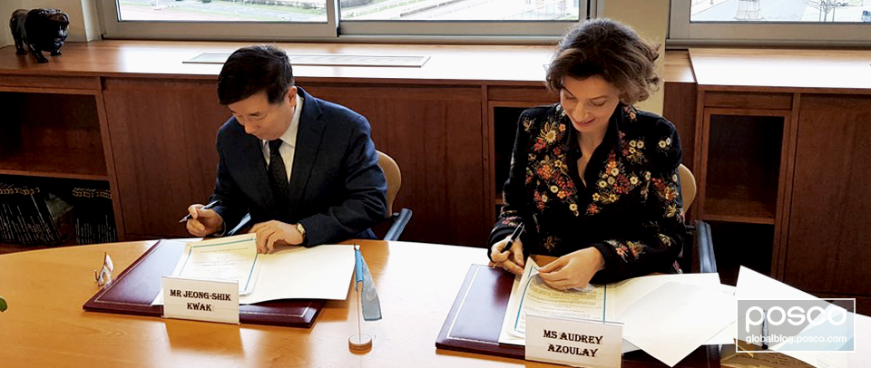 Jeong-sik Kwak, head of the ER Office of POSCO, and UNESCO Director-General Audrey Azoulay sit side by side signing documents.