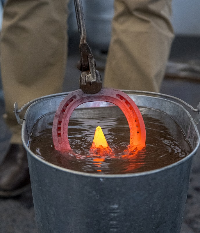 A horseshoe getting quenched in cold water.