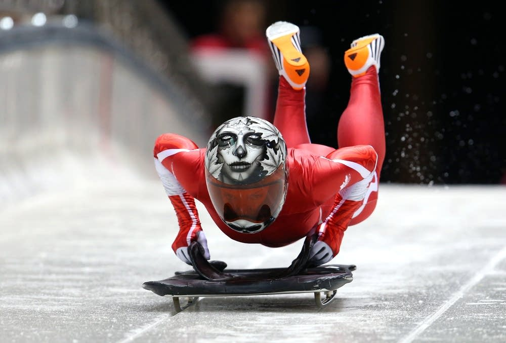 A skeleton athlete going down the track on a sled.