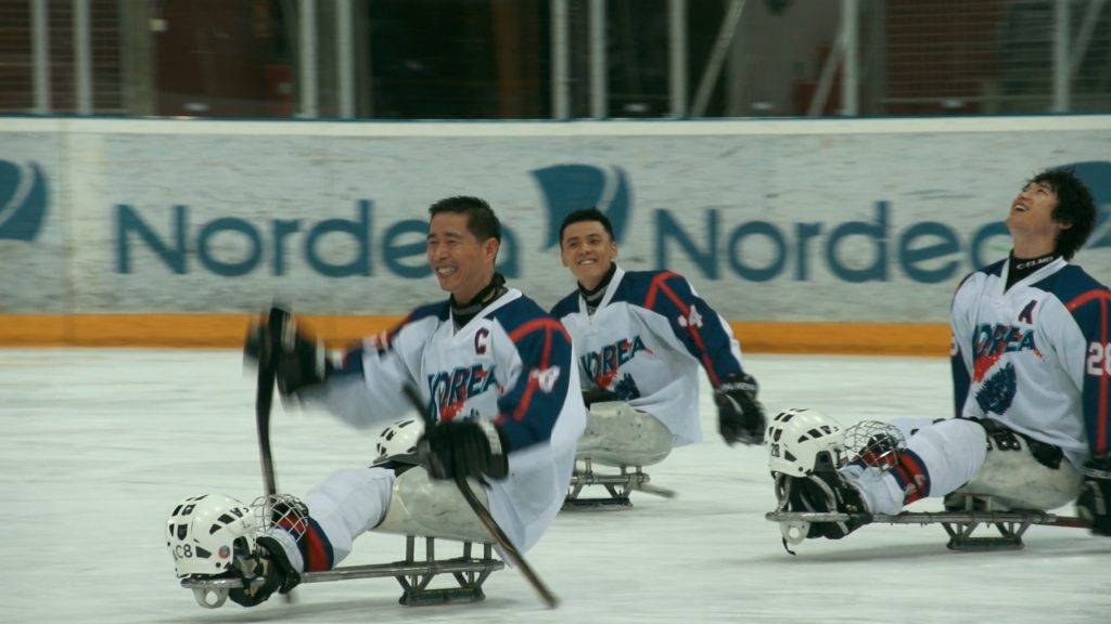 The Korean National Para Ice Hockey Team smiling during a game.