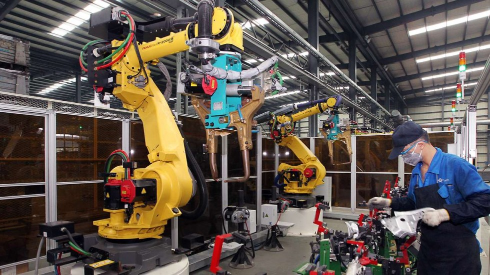 A worker works with robots in a manufacturing factory.